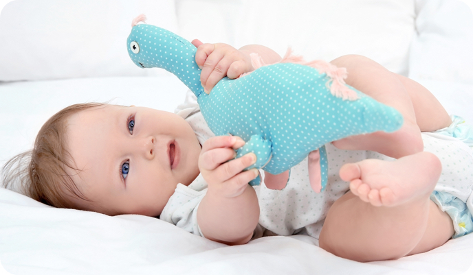 Baby playing toy dinosaur